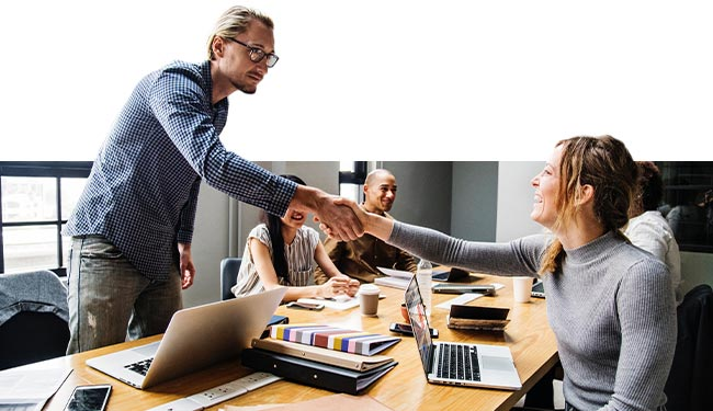 A man and a woman shake hands over a busy workspace